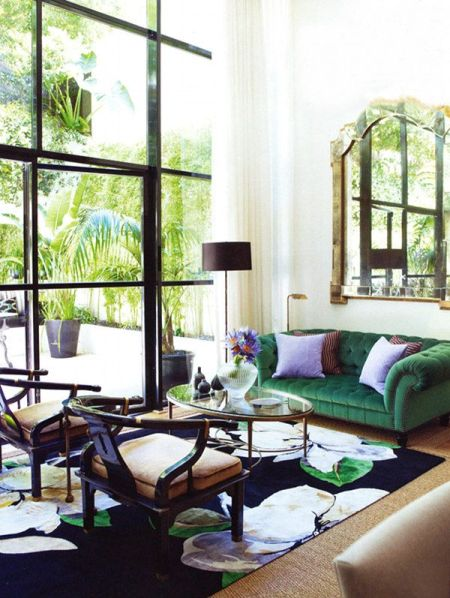 modern living room with green couch and huge windows