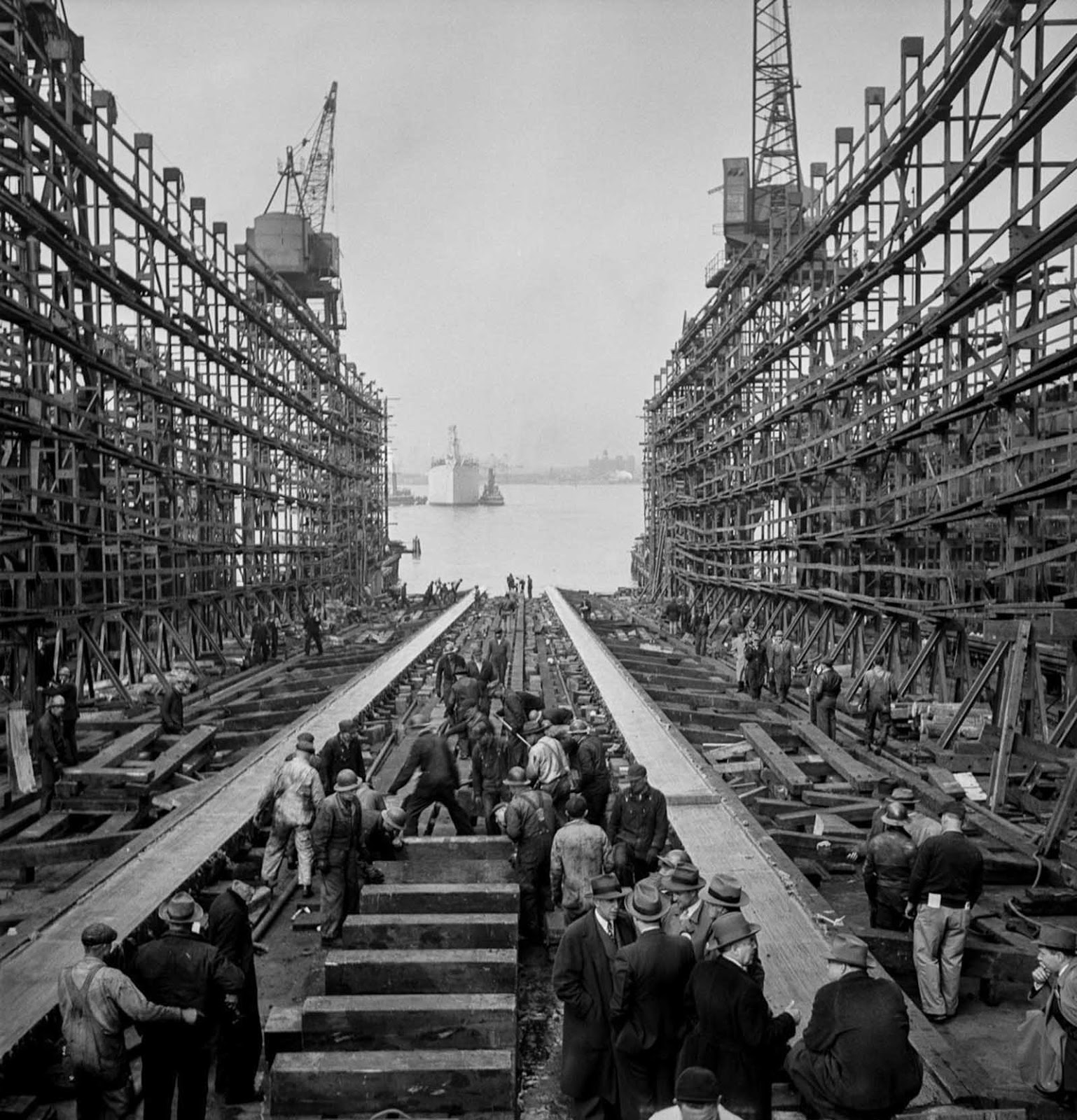 After a launch, workers fill the way and prepare to build another ship.