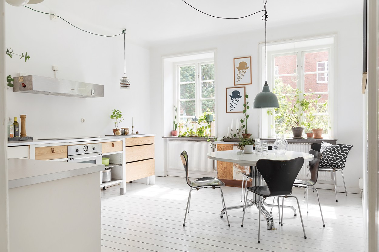 minimalist kitchen inside of a scandinavian farmhouse with white painted floors