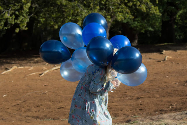 A girl with a bunch of balloons for her head