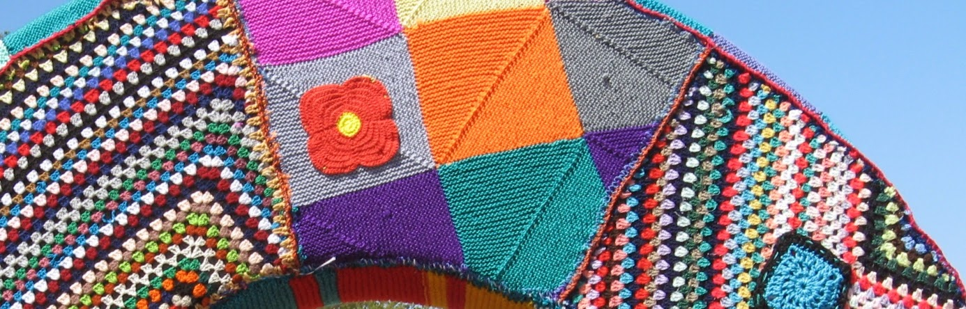 "A section of the ""Rhythm Sculpture"" yarn bomb project which is described in the blog post ""Stitch For Summer: A Colourful Rhythm"" posted on 23 February 2013. This photograph shows a patchwork of knitted mitred squares in solid colours, one of which has a red flower with a yellow centre appliquéd ont it.  The patchwork is flanked by blanket sized multicoloured granny squares, one of which has a blue patch appliquéd on it. These crochet fabrics cover an arch-shaped section of an outdoor sculpture."