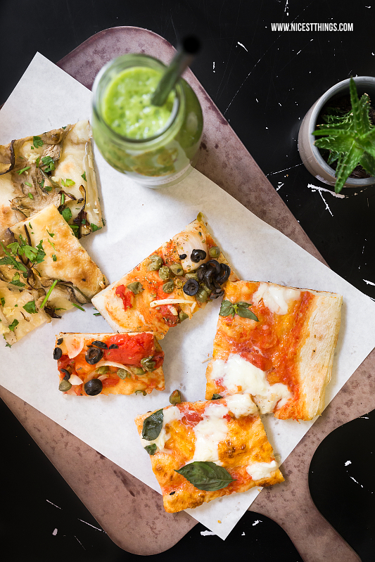 Pizza von oben auf Holzbrett mit Smoothie bei Unter Freunden