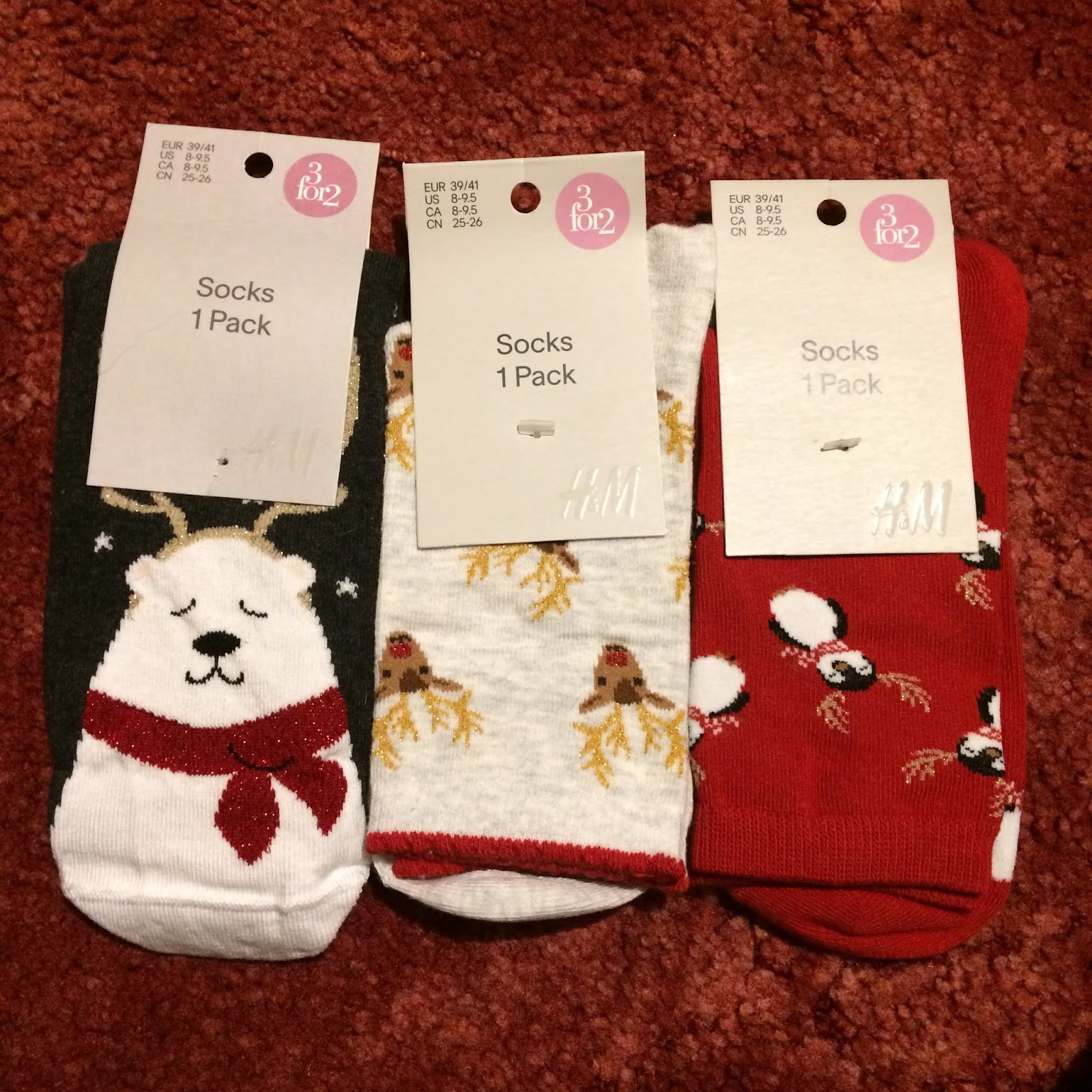 Three pairs of festive socks, one navy blue pair featuring a polar bear weaing a red scarf and antlers, a pale grey pair with a repeated pattern of Rudolph's head, and a bright red pair with a repeated pattern of a penguin wearing antlers.