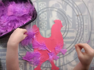 Three year old adding more feathers to her rooster craft
