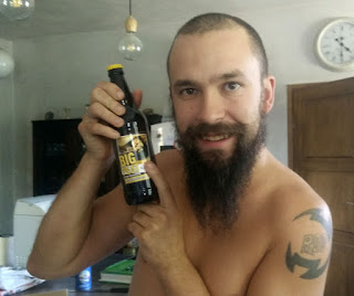 A bearded man with a beardy bottle of beer