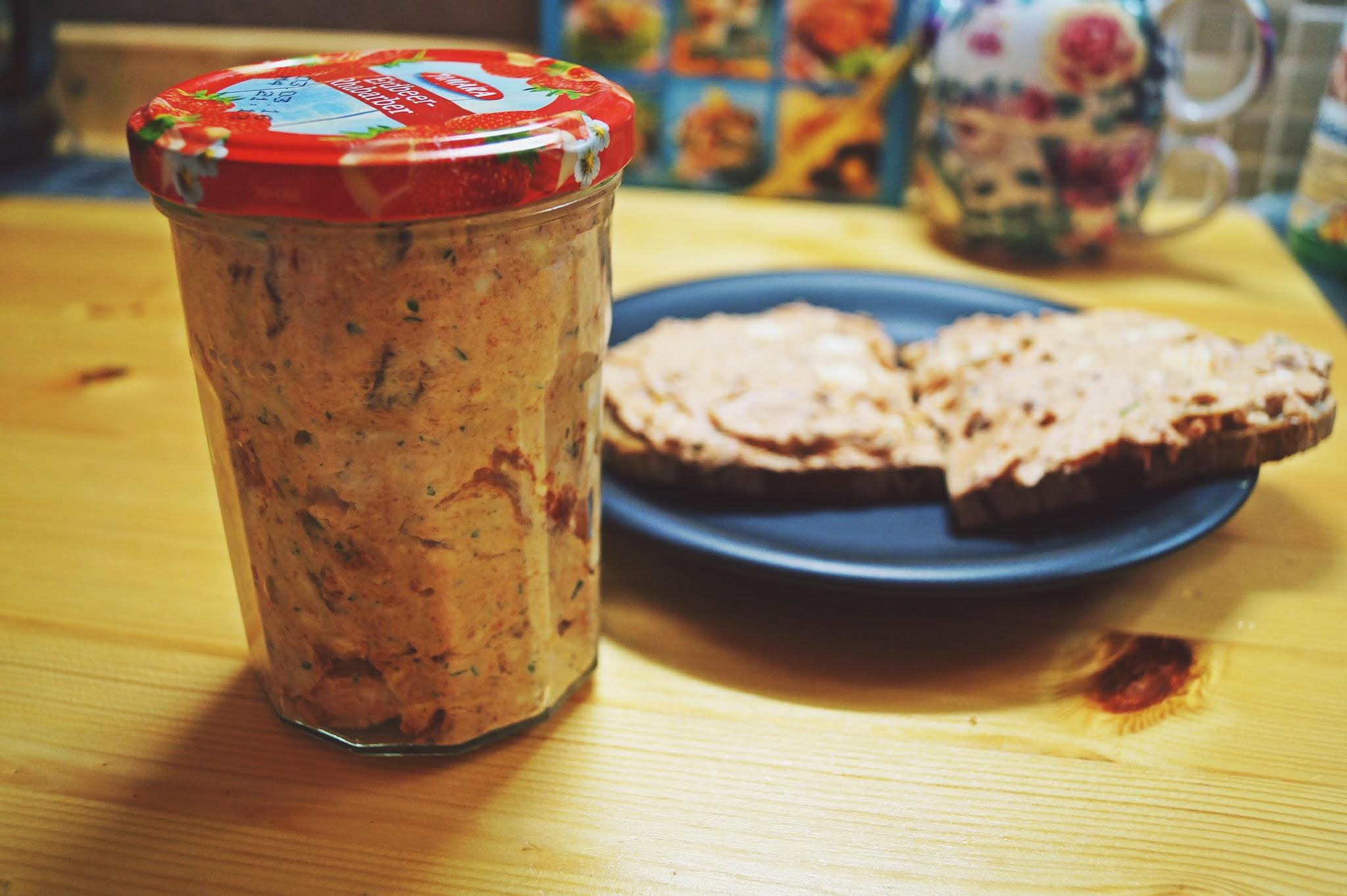 Frischkäseaufstrich im Glas und auf dem Brot