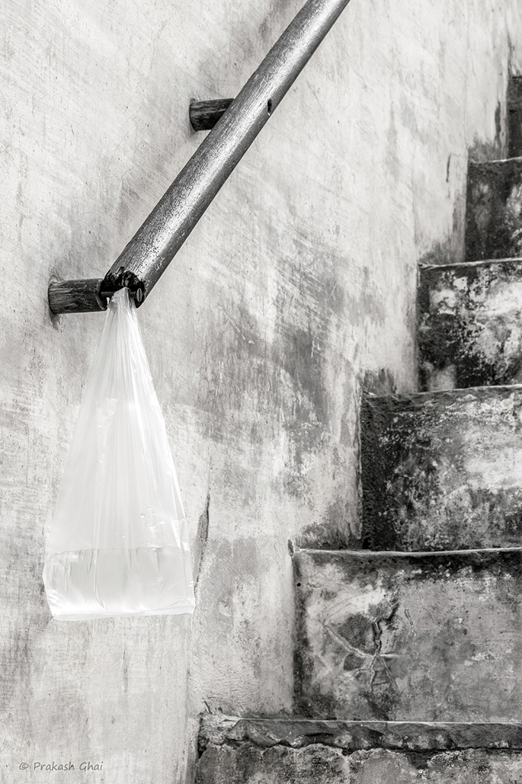 A minimalist photo of A plastic bag containing water, hung on the railing of a staircase.