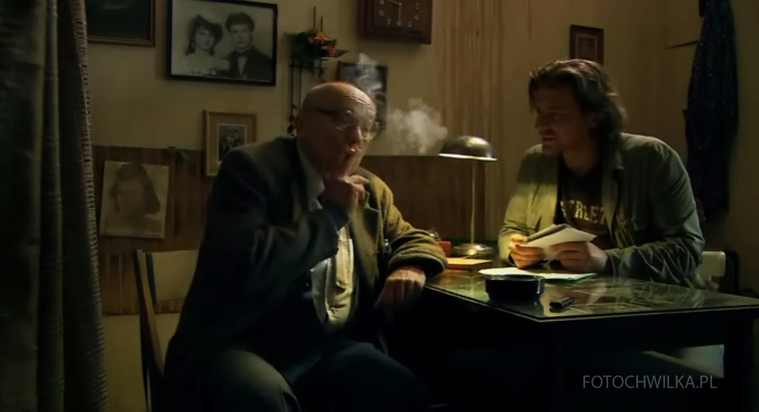 Rezerwat. Kadr z filmu. Marcin siedzi w zakładzie fotograficznym.