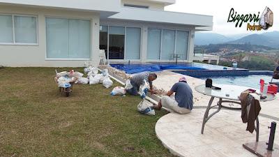 Bizzarri, da Bizzarri Pedras, enchendo a canaleta com pedregulho do rio na cor bege número 2 a 4, sendo canaleta para captar água que cai no piso da piscina em casa em condomínio em Atibaia-SP. 18 de maio de 2017.