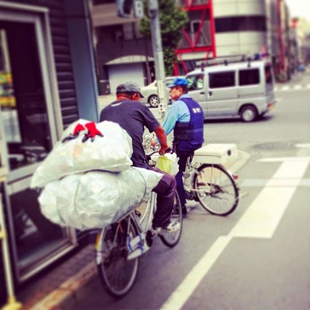 Homeless person and policeman on bicycles, Asakusabashi, Tokyo