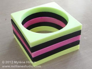 Handmade licorice allsorts resin bangle stack of green, black, pink, black and yellow square bangles.