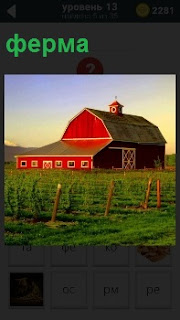 Вдали за полем расположен красный дом в виде фермы. На переднем плане ограждение столбами и проволока между ними
