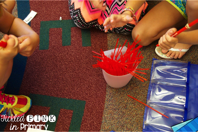 students helping sort place value straws on the rug for end of the year organization
