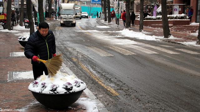 Coreano limpiando la nieve en una calle de Seúl