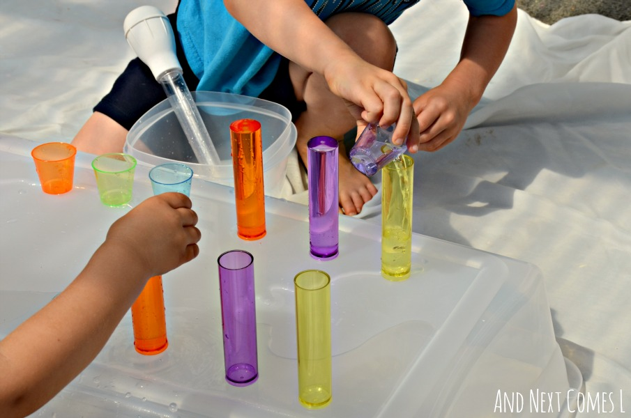 Practicing fine motor skills by pouring water into colorful cups from And Next Comes L