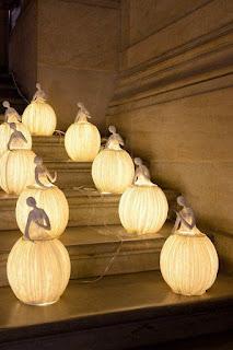 Uma dupla de artistas franceses formada por Sophie Mouton-Perrat e Frédéric Guibrunet cria, entre outras, sensacionais esculturas-luminárias feitas de nada menos que papel machê. Descrição: Em um canto de uma escadaria de mármore sobre cinco degraus, nove luminárias acesas distribuídas duas a duas em cada degrau debaixo para cima, sendo a última, na parte central, no topo. As delicadas luminárias têm a forma de bailarinas com a saia bem rodada em forma de balão gomado, cada bailarina tem uma expressão gestual e remetem às de caixinha de música.
