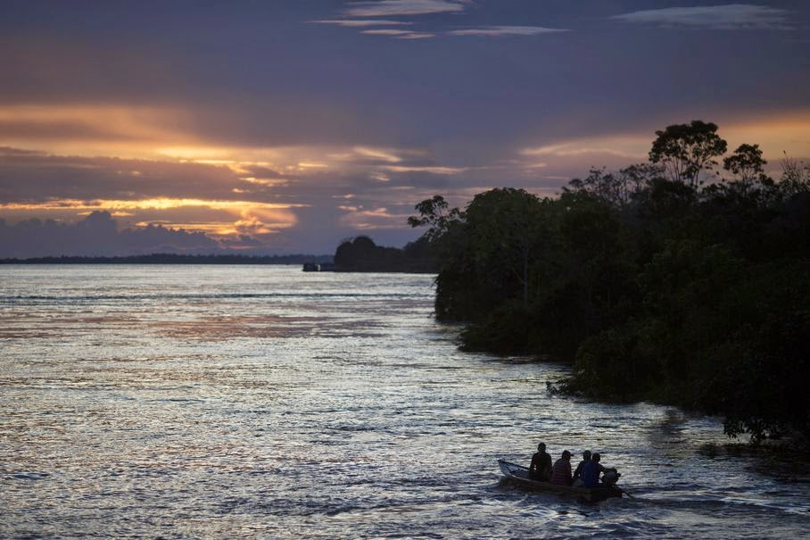 In this May 22, 2014, photo, a small boat navigates on the Solimoes river near Manaus, Brazil. While most tourists opt for speedboats for their jungle journeys, a riverboat day trip can give even Cup visitors on a tight schedule a taste of authentic Amazonian life.