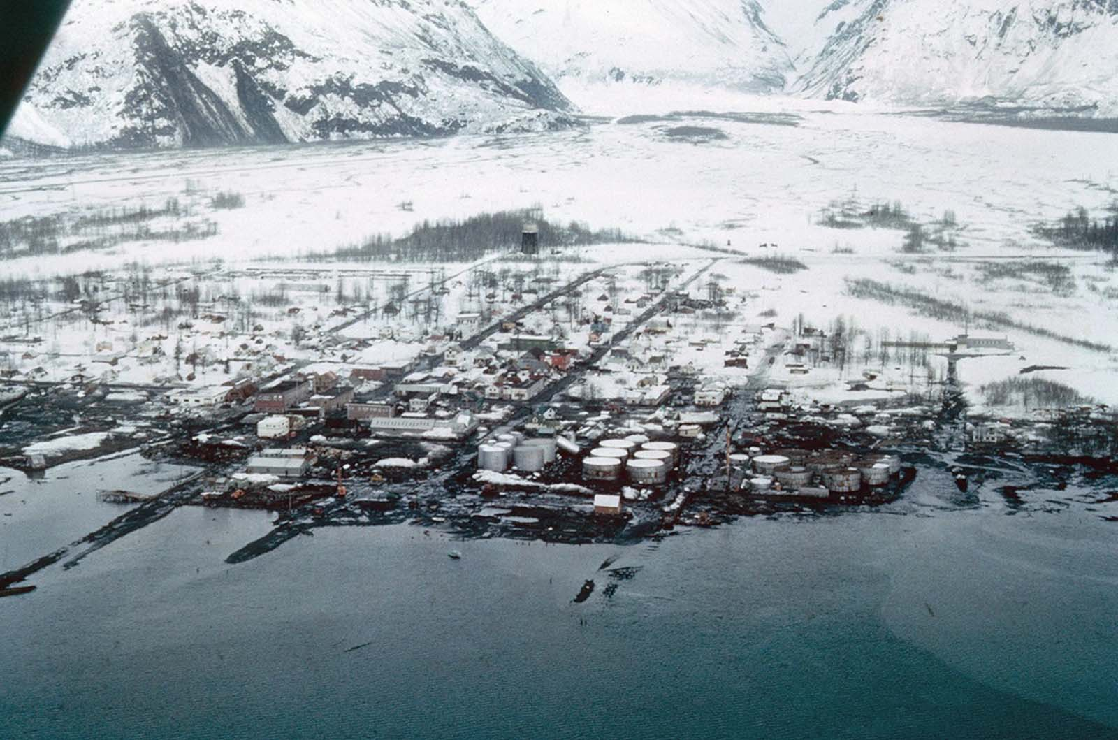 A view of the destruction of Valdez, Alaska. Thirty-one residents died during the earthquake and subsequent tsunami. Instability and vulnerability to future tsunamis made the old town site too dangerous to rebuild, so the town was relocated several miles west to more stable ground, and rebuilt.