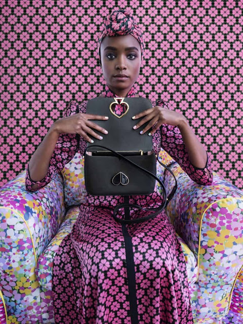 Kiki Layne  in a flower dress, holding a black Kate Spade handbag by Tim Walker