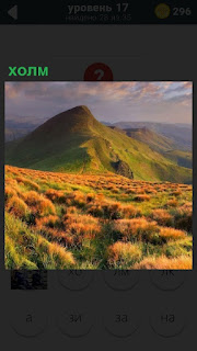 Через поляну виден небольшой холм в долине