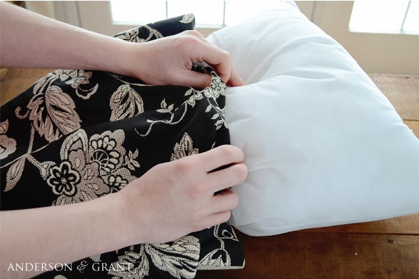 Stuffing pillow inside black and white pillow cover.