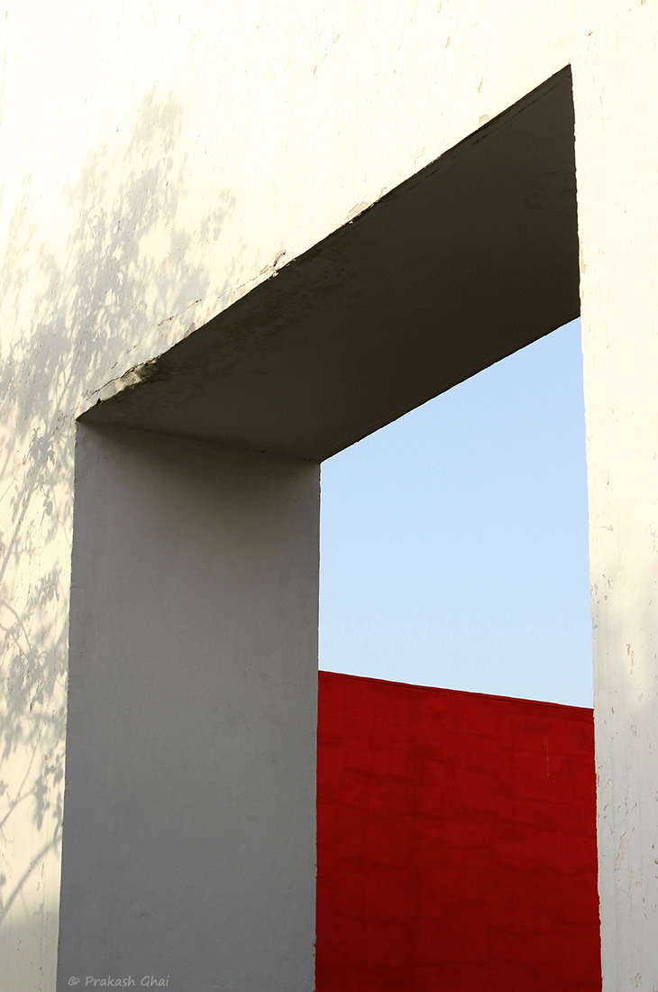 A Minimalist Photo of A red wall engulfed by the blue sky, as seen through the big white window.