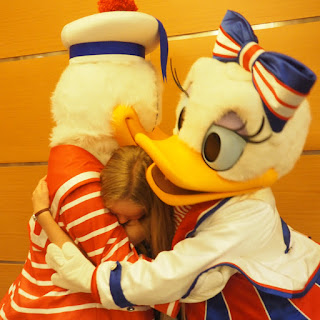 Girl gets a hug from the Disney ducks