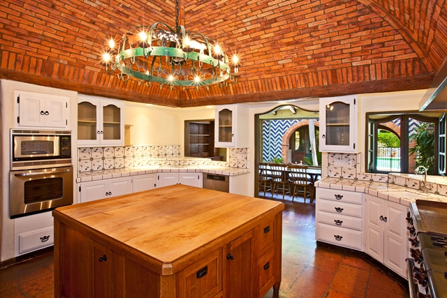 White kitchen of Mel Gibson's house with bricks on the ceiling