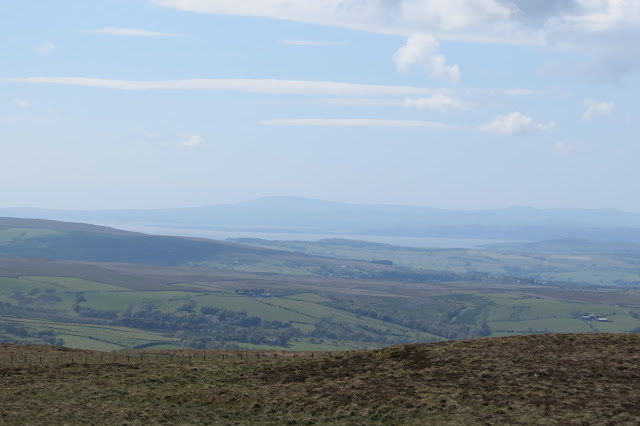 A view across Lancashire farmland to the waters of Morecambe Bay, with hazy outlines of Lake District fells beyond it.