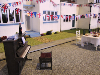 Miniature scene of a piano at a VE Day street party in front of a row of Art Deco houses.