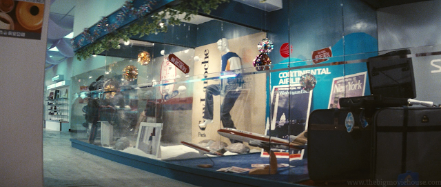 Jackie Chan pushes a man through several panes of glass with a motorcycle.