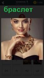 На девушке одет браслет на руку и на шее висит прекрасной красоты ожерелье по цвету такое же