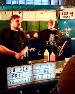 A tall dark haired man in a black uniforn behind a rectangular metal table with two rectangular boxes saying burgers fries and drinks on a bright background