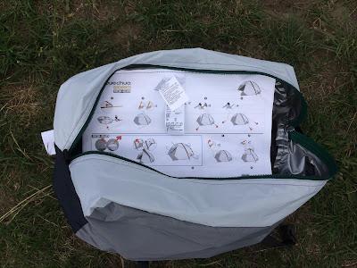 Eine weiße Tasche liegt offen auf einer Wiese. In der Tasche sieht man eine bebilderte Anleitung