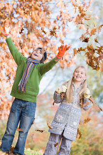 Photo of two children playing in the autumn leaves
