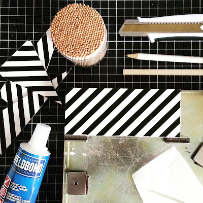 Flat lay on a cutting mat, with black and white striped wood pieces, glue, toothpicks, utility knife, pencil, and gluing jig laid out.