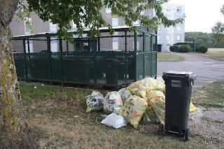 Local poubelle grillagé et tas de sacs jaunes devant immeuble