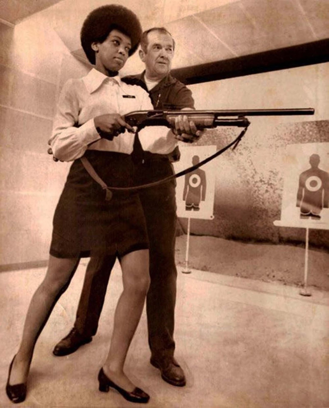 Saundra Brown, the first black woman on the Oakland police force, gets instructions on how to shoot a shotgun, 1970.