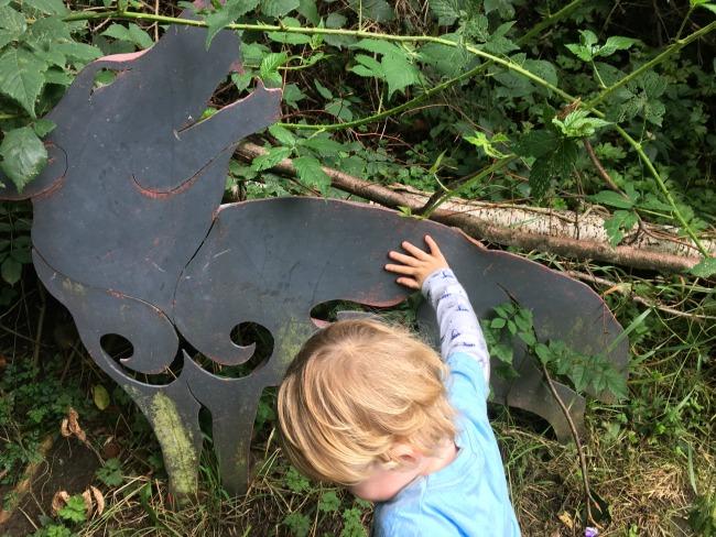 toddler-touching-metal-wolf-sculpture-cwm-carn-forest