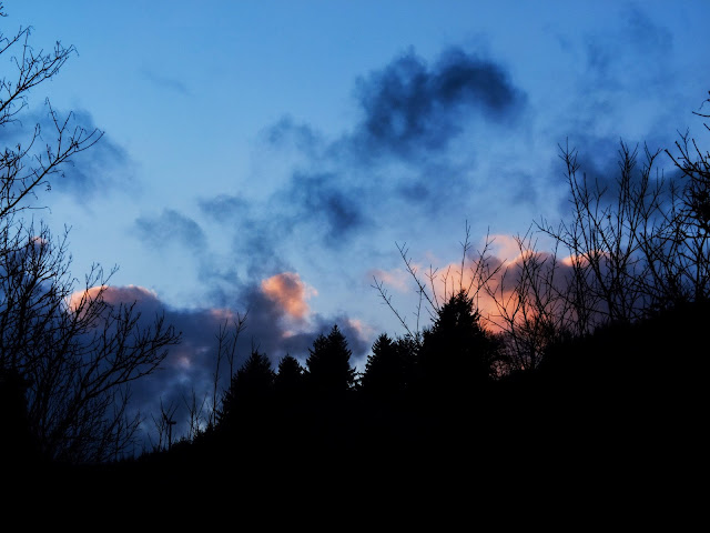 End of a sunset over a hillside with big navy dramatic clouds.