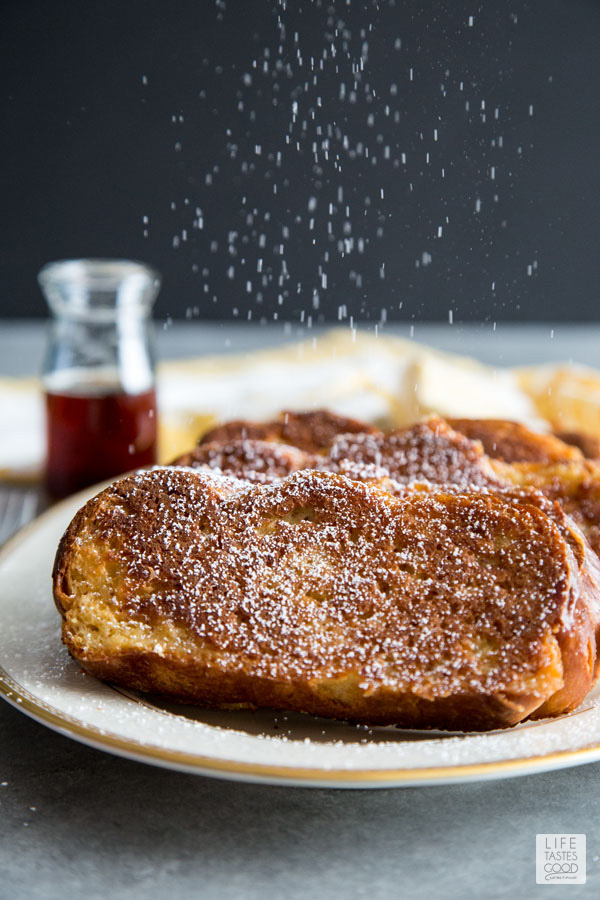 Oven French Toast on a white plate with a sprinkling of powdered sugar raining down it