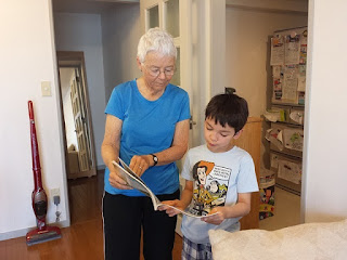 woman showing book to young boy