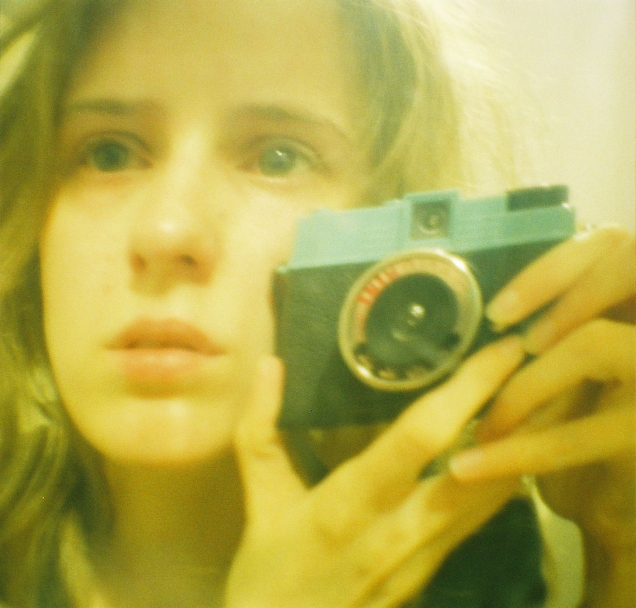 A slightly distorted image of a young woman taking her own picture in the mirror with a Lomo Diana Mini.