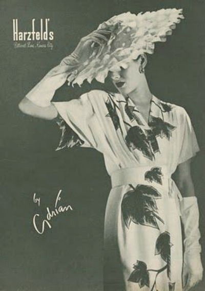 Model in Print Dress, Large Hat and white gloves in 1946 ad for Adrian Design for Harzfeld's