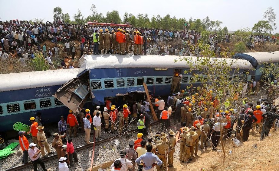 Rescuers and onlookers gather around damaged coaches of a derailed train near Anekal, about 40 kilometers south of Bangalore, India, Friday, Feb. 13, 2015. A train derailed after hitting a boulder that had fallen on the track in southern India on Friday, killing more than 10 people and injuring dozens, officials said.