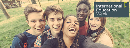 A diverse group of five students are smiling at a camera with grass and trees in the background. There are five students; three males, two females. It appears to be a selfie.