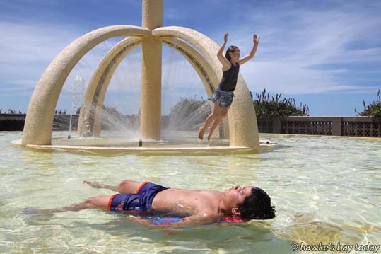 Jumping: Kelly Taylor, 9; Reclining: Kingston Taylor, 10, siblings, Napier, in the pool under the Spirit of Napier, Marine Parade, Napier, in hot sunny spring weather. photograph