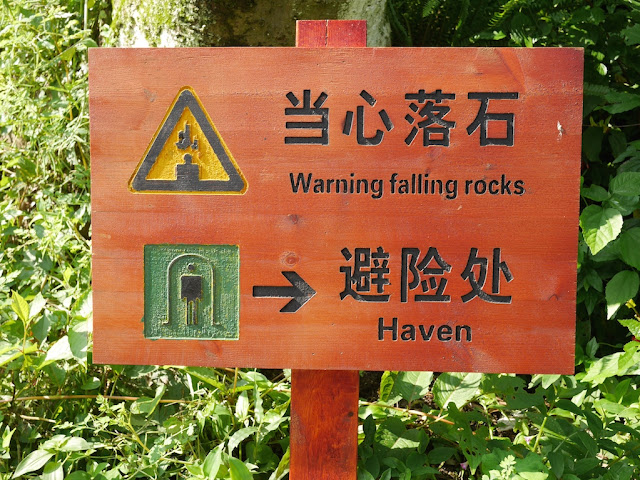"Sign with a falling rocks warning and directions to a ""haven"""