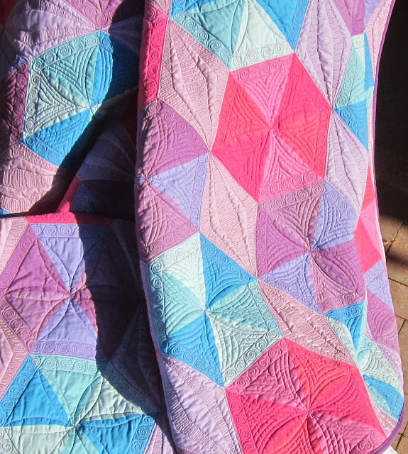 http://quiltparadigm.blogspot.com/2014/05/halographic-hexigonal-triangles-its-wrap.html