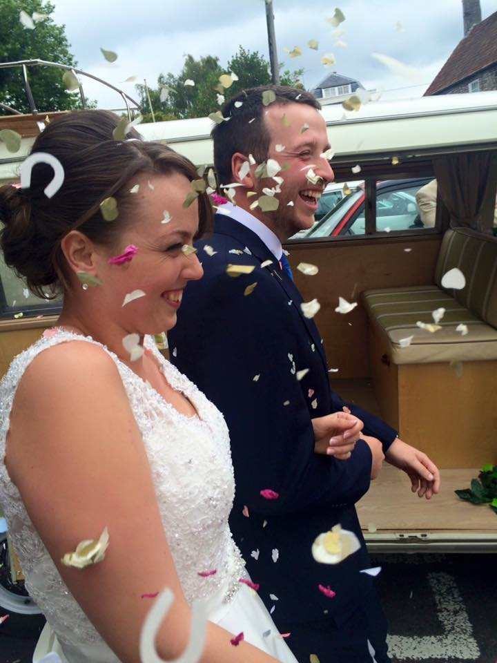 The gorgeous bride and groom being showered with confetti